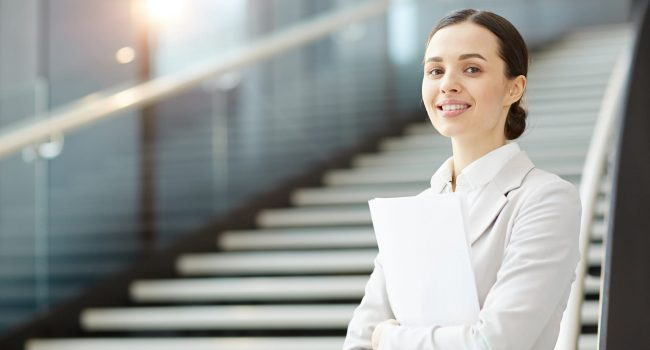 Young agent with papers standing by staircase in airport lounge and looking at camera