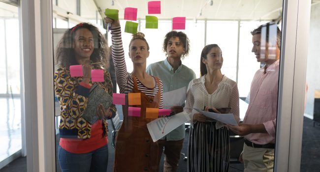 Front view of multi-ethnic business colleagues discussing business strategy over sticky notes in modern office