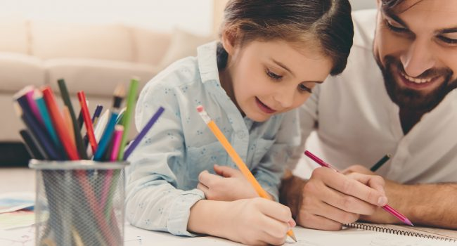Cute little girl and her handsome father are drawing and smiling while playing together at home