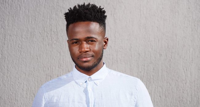 Close up portrait of handsome young african man with beard standing looking serious