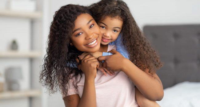 Love between parent and child. Positive little black girl hugging her mom on bed at home. Young African American woman and her daughter embracing, spending quality family times together indoors