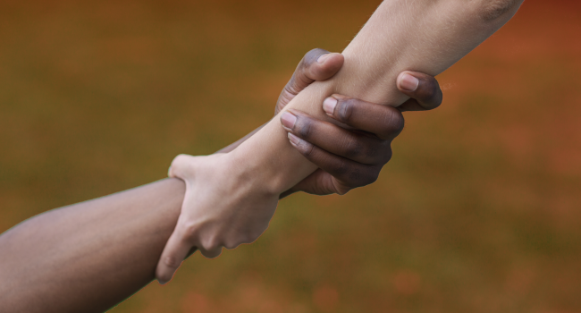 multiethnic-friends-helping-hand-outdoor-copy-spac-ETVAZ5Y