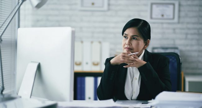Pensive Vietnamese female attorney sitting in front of computer